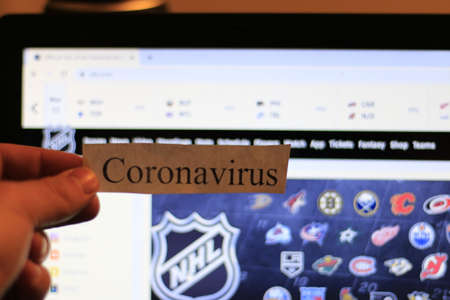 London Canada, March 12 2020: Editorial illustrative photo of coronavirus in front of the NHL website. The NHL has cancelled the season temporarily