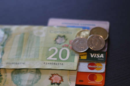 London Canada, December 25 2019: Editorial image of Canadian currency and credit cards. Theme of debt and spending