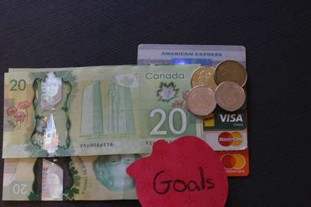 London Canada, December 25 2019: Editorial illustrative photo of credit cards and money with a note that says goal. Theme of paying debt and saving