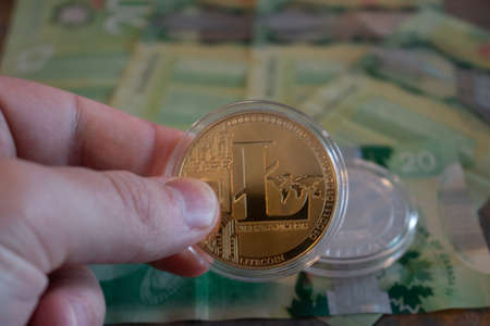 London Canada, January 24 2020: Editorial Illustrative photo of Holding a litecoin over currency. Concept of decentralized currency system