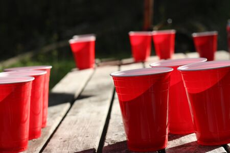 Red party cups themed background template. White backdrop. Alcohol container on its side. People dancing hands up in the air. Empty blank copy space. Event marketing and promotion.