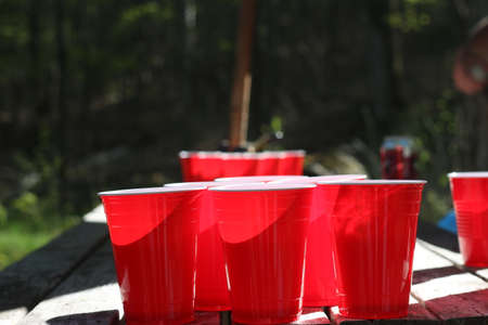 beer pong cups set up outside on picnic table 写真素材