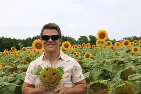Young handsome happy man with sunflower in hands standing in wheat field. Country, agricultural. Standard-Bild