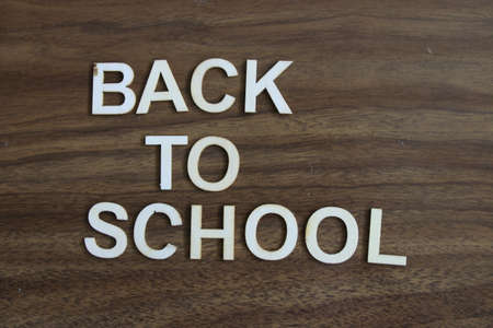 back to school wrote out on a wooden background
