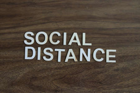the term social distance on a wood background