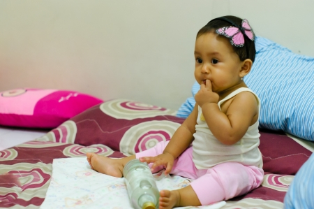 cute baby sit on her bed with butterfly hairpin photo