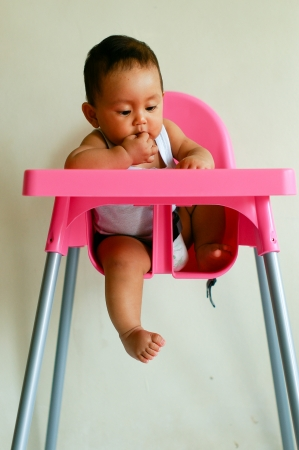 baby on chair: baby sit in her pinky baby chair and smile Stock Photo