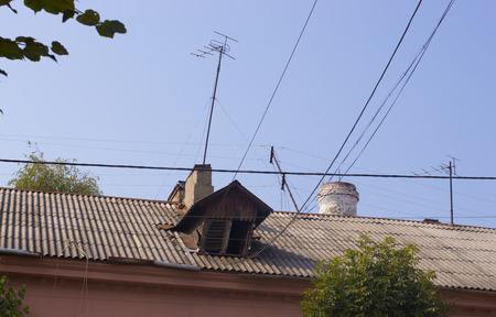 dormer: Rustic Dormer on Slate Roof Beneath Blue Sky