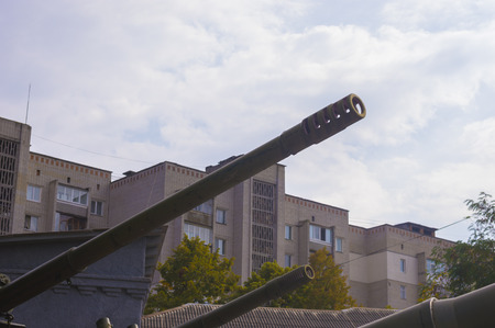 totalitarianism: Artillery Gun Muzzles on Background of Residential Buildings