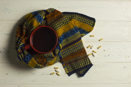 ard: Mug of Tea, Scarf, and Pills: Winter Illness Safety Concept