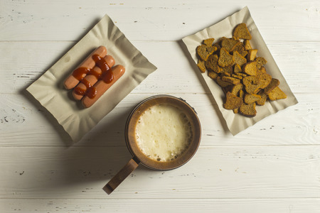 angle bar: Mug of Beer, Sausage, and Dried Bread on Wooden background