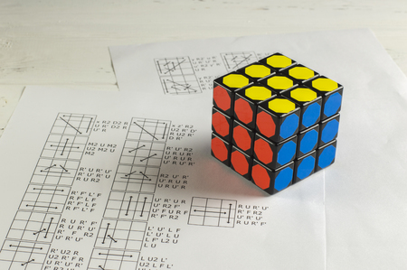 KIEV, UKRAINE - MARCH 25: Rubiks Cube on Background of Papers with Solving Algorithms
