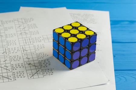 algorithms: KIEV, UKRAINE - MARCH 25: Rubiks Cube on Background of Papers with Solving Algorithms