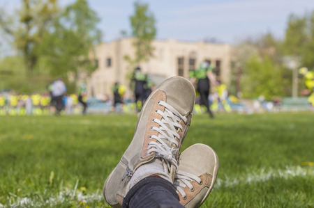 Close up of female watching football game: snickers shoes on background of American football match