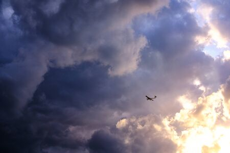 Tiny plane in front of a colorful and cloudy sky in vivid evening athmosphere