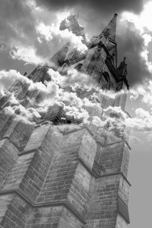 bewitched: The ancient tower stands out against the sky and the clouds completely wraps it in a mystery glow Stock Photo