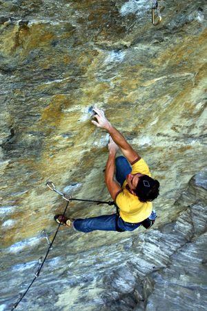 Strong free climber climbing a hard wall Standard-Bild