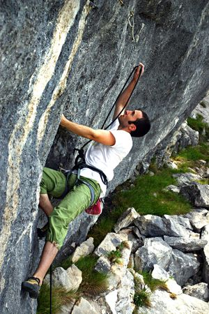 The free climber is fighting against a hard wall