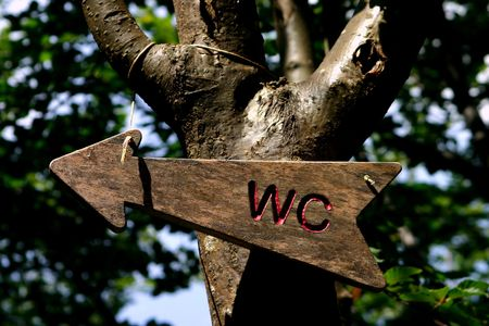 In the camping, the wooden WC sign indicates the right direction to reach the bathroom