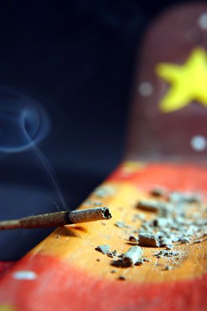 flutter: The incense is burning and spirals of smoke flutter in the air while the ashes stands on the incense boat