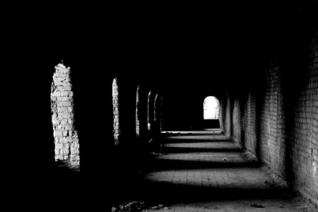 An old dark passage with the light coming from the arches