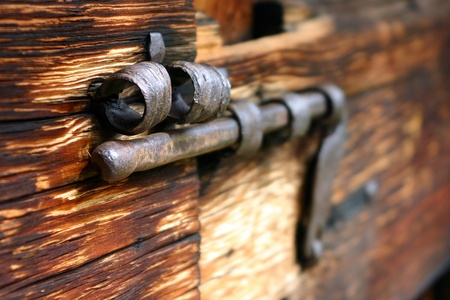Old rusty bolt on a wooden door photo