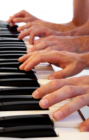 ensemble: Six hands playing simultaneously on a grand piano with bright white background Stock Photo