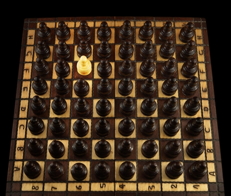 A white pawn is the only one surrounded by the other black pawns Stock Photo - 15222892