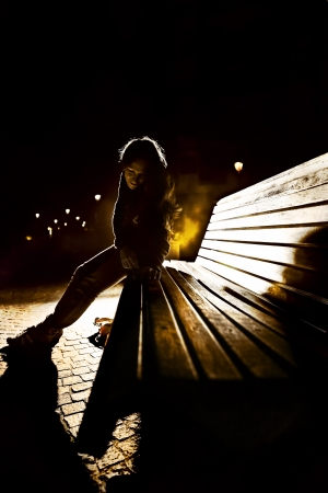 Girl sitting on a bench in the night mysterious atmosphere photo