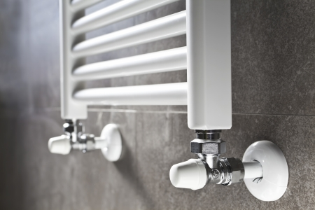 White bathroom heater closeup on gray wall