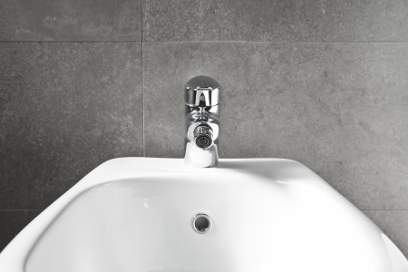 White porcelain bidet closeup on gray wall  photo