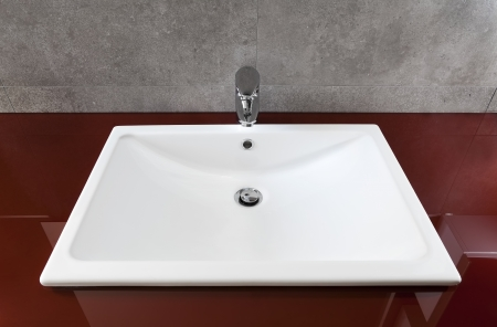 White bathroom sink on a red translucent board  photo
