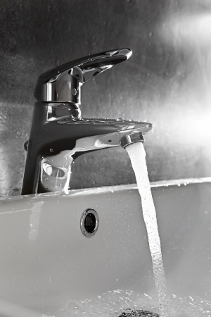 Bathroom sink silhouette lighted by backlight with water splash Stock Photo