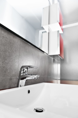 Bathroom white porcelain sink closeup with red furniture