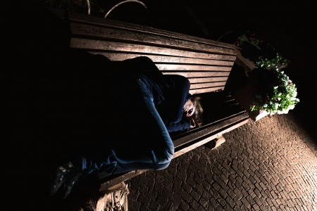 Homeless girl sleeping on a bench in the night mysterious atmosphere photo