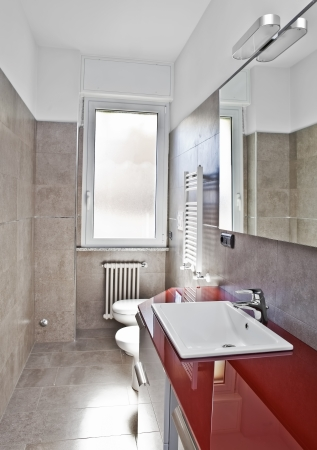 Red bathroom with toilette, bidet, heater, lavabo and mirror in soft hdr  Stock Photo
