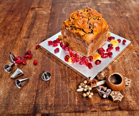 Christmas cake with red berries and metal tips and xmas decorations