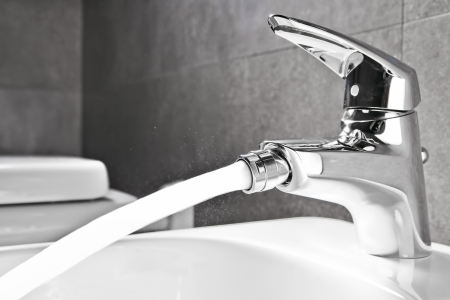 Bathroom bidet faucet closeup with water flowing photo