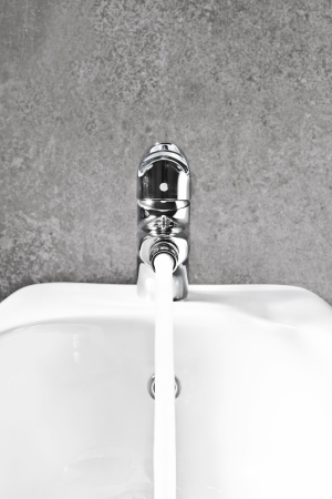 lavabo: Bathroom bidet faucet closeup front with water flowing