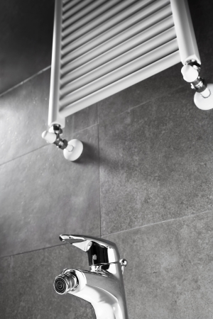 Bathroom faucet and heater on a gray wall
