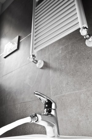 Bathroom faucet with water and heater on a gray wall