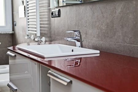 Red bathroom with toilette, bidet, heater, lavabo and mirror