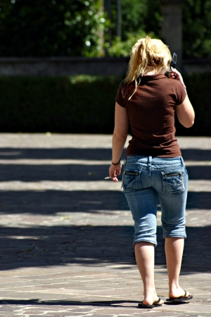 A blonde woman is smoking and using her mobile phone  She is walking with a cigarette in her left hand and the cell-phone in the other one photo
