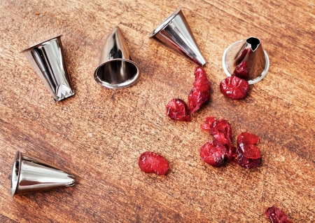 metal tips: Pastry bag metal tips and red candieds on a wooden table  Stock Photo