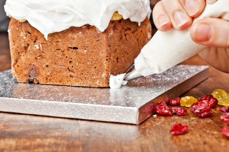 piping: Decorating cake with a pastry bag full of cream  Stock Photo