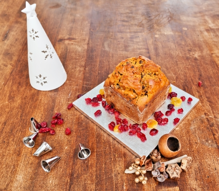 Christmas cake and white candle on wooden table