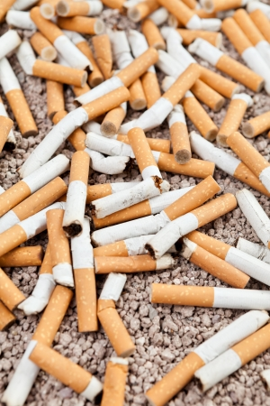 Ashtray full of smoked fallen cigarettes in the sand  photo