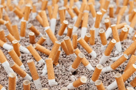 Ashtray closeup full of smoked cigarettes in the sand Stock Photo