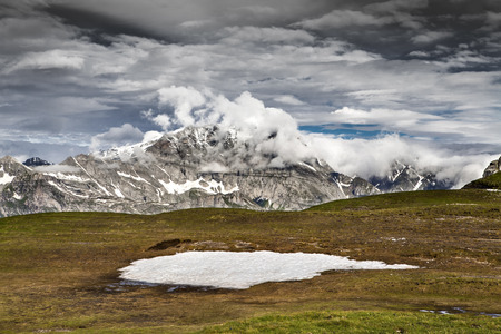 Alpine landscape with green grass, blue sky and heavy white clouds  Stock Photo