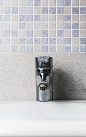 Faucet front view and mosaic tiles wall Standard-Bild